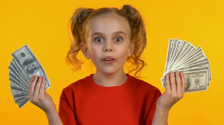 regozijo : Cheerful little girl showing dollar bunches at camera and smiling, first income Stock Footage
