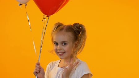 koketa : Little coquette girl with balloons sending air kiss on camera, first sympathy
