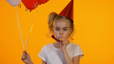 bóia : Upset birthday child with balloons using party blower, celebrating party alone Stock Footage