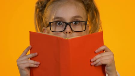 ansiklopedi : Little smart kid in eyeglasses reading encyclopedia shocked by interesting facts Stok Video