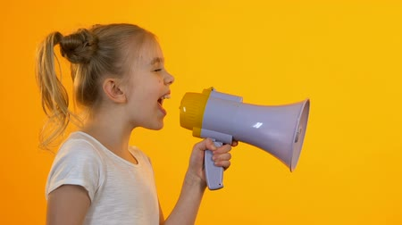 atenção : Little female child shouting in megaphone trying to be heard by parents, protest
