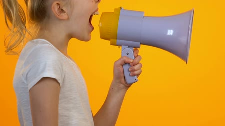 megafon : Female kid shouting in megaphone, relieving stress against orange background