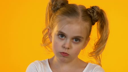 grimacing : Offended little child angrily looking into camera against orange background
