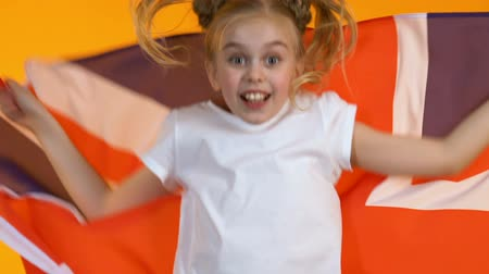 regozijo : Funny child fan waving flag of Great Britain, cheering for national sports team Stock Footage