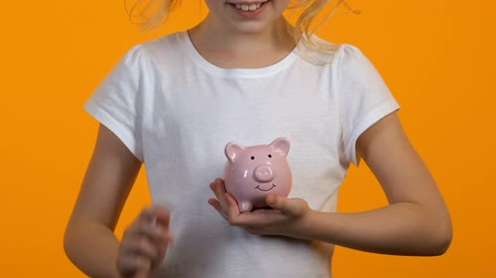 ganhos : Female child putting coins into piggy bank, savings and personal budget, finance