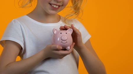 kumbara : Little girl stroking piggy bank, personal savings and budget, planning future Stok Video