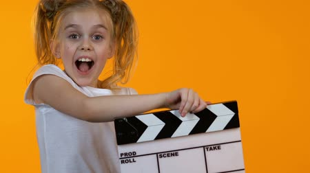 sinematografi : Funny little kid using clapboard and smiling on camera, junior acting school