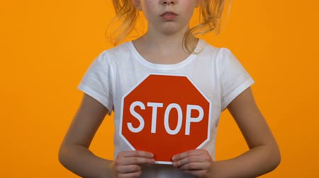 abused : Little girl holding stop sign template in hands, childrens rights protection
