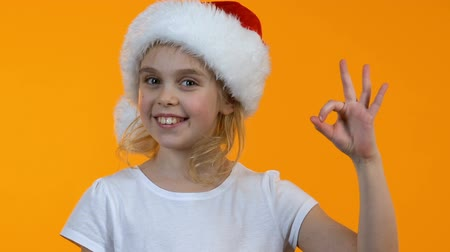 okey : Smiling little santa kid showing ok sign and winking on camera holiday discounts