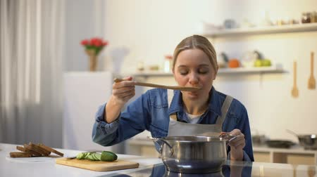 unpleasant smell : Girl disgusted with stinky meal on stove, spoiled ingredients, untasty food Stock Footage