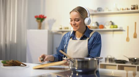 soup pans : Positive girl listening music and cooking vegetables, healthy low-calorie eating Stock Footage