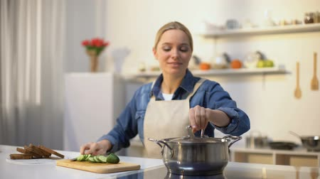 unpleasant smell : Young woman smelling cooked soup with disgusted face expression, spoiled food Stock Footage