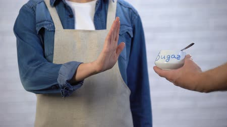 adoçante : Person in apron gesturing no sugar in cooking, risk of diabetes and obesity