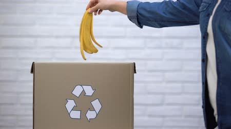 biodegradable : Person throwing banana peel into trash bin, organic waste sorting, awareness