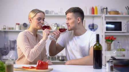 víno : Young couple drinking wine in kitchen, chatting and relaxing together, romance