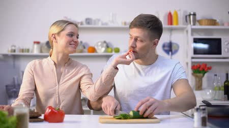 calorias : Young happy family flirting, cooking salad of raw vegetables, healthy eco food Stock Footage