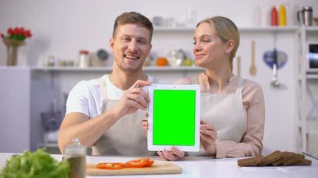 rekomendacja : Cheerful couple holding tablet with green screen, online food shopping template Wideo