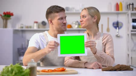rekomendacja : Young smiling couple showing tablet with green screen, culinary courses template
