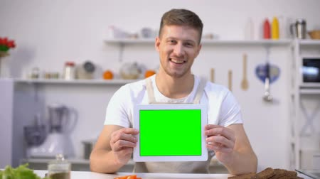 ajánlás : Cheerful man holding tablet with green screen, cooking blogs and apps template