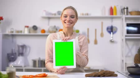 rekomendacja : Beautiful girl holding tablet with green screen, easy cooking mobile application