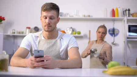 privacy : Handsome man typing message in phone, jealous wife peeking, cheating in marriage