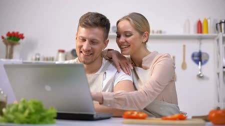 culinária : Young couple looking for food recipes on websites and laughing, kitchen novices