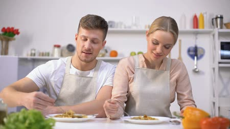 pasta maken : Young couple eating pasta, smiling on camera, concept of quick and easy food