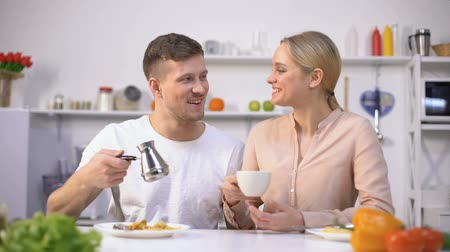 стимулятор : Handsome man pouring brewed coffee to young lady, energy boost in morning
