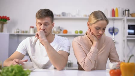 incomprensione : Young couple sitting silently in kitchen after argument, crisis in relationship