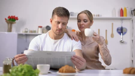hot news : Young husband reading newspaper with wife drinking coffee, morning together