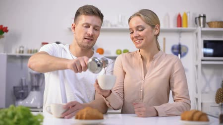 варивший : Handsome man pours brewed coffee to cute girl and gets kiss, romantic morning