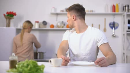 equal : Hungry man eagerly waiting for dinner, wife cooking on background, starvation
