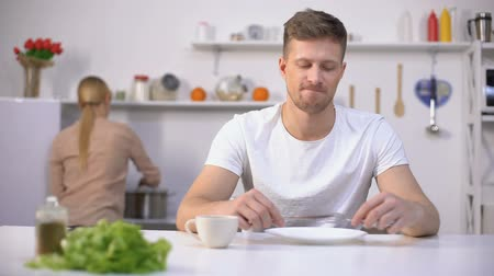 starving : Positive man waiting for dinner, young wife cooking soup on background.