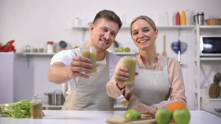 rekomendacja : Joyful couple holding spirulina smoothie, recommending healthy drink, vitamins Wideo