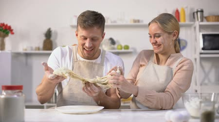eleven : Carefree couple clumsily kneading dough, having fun in kitchen, inept chefs Stock mozgókép