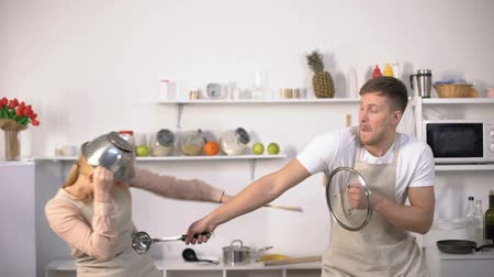 culinária : Carefree couple fighting with kitchenware, pretending knights, having fun Stock Footage
