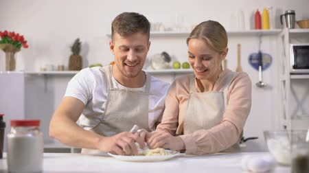 piada : Happy couple clumsily kneading dough, spending fun time together in kitchen