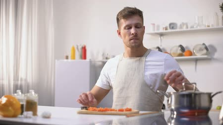unpleasant smell : Young man disgusted with stinky meal on stove, spoiled ingredients, untasty food