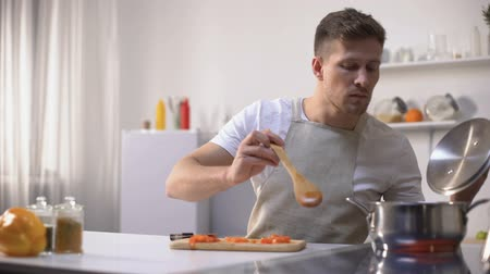 grimacing : Young man tasting cooked food with disgusted face expression, funny grimacing