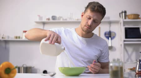 aveia : Handsome male eating corn flakes with milk, nourishing and healthy breakfast
