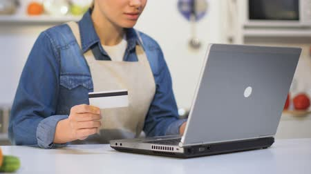gênero alimentício : Young woman in apron inserting credit card number on laptop, product shop online Stock Footage