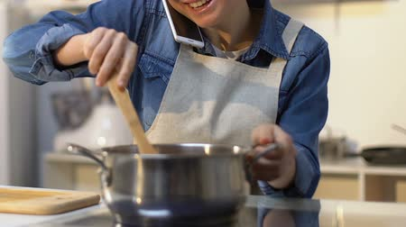 суп : Happy girl in apron stirring soup in pan with wooden spoon and talking on phone