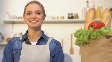 kitchen paper : Smiling woman looking at paper bag with fresh bread, fruits and vegetables