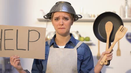 perdedor : Inexperienced lady with colander on head holding kitchen utilities and help sign