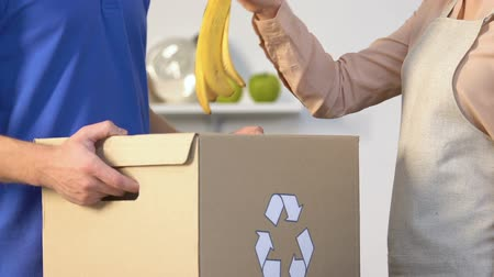 elválasztás : Housewife throwing banana peel into box for organic garbage, waste recycling Stock mozgókép