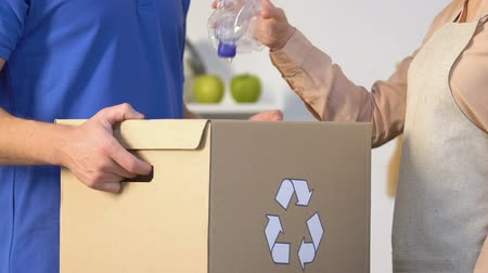 litter box : Lady throwing plastic bottle into special box with recycling sign in mans hands Stock Footage