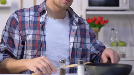 condimento : Man cooking breakfast, adding ground pepper into frying pan, seasoning dish Vídeos