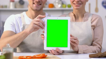 блог : Cheerful couple in aprons holding green screen tablet sitting in kitchen receipt