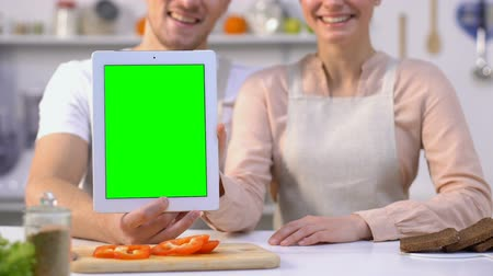 kötény : Pretty family couple holding green screen tablet and showing thumbs-up, blogging