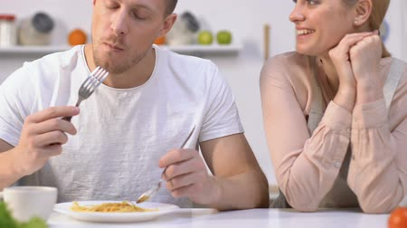 tápanyagok : Tactful guy trying girlfriends tasteless dish, pretending that it is delicious